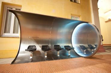 PEDRO MORA. Bus stop, 2001. 360 x 210 x 210 cm. Acero pulido inoxidable, espejos, neón, fotografía y 4 asientos